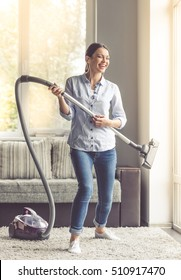Beautiful young woman in earphones is using a vacuum cleaner for imitating playing guitar and smiling while cleaning her house