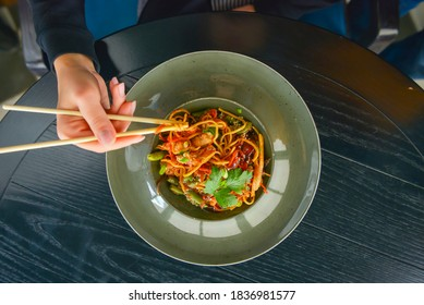 Beautiful young woman eating chinese food called Wok with chopsticks. Wok with meat and fried asparagus in a plate. Still life, eating out in restaurant concept.