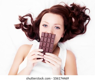 beautiful young  woman eating chocolate in bed at home