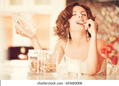 Beautiful young woman eating cookies