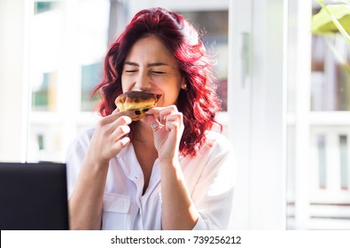 Beautiful young woman eating donuts