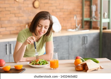 Beautiful young woman eating fresh salad in kitchen