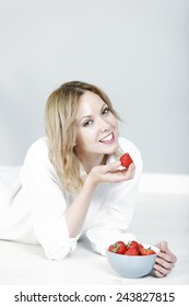 Beautiful young woman eating fresh strawberries at home