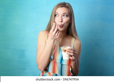 Beautiful young woman eating ice cream on color background