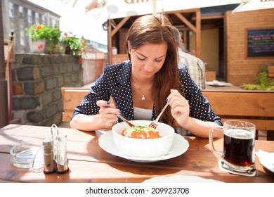 Beautiful young woman eating lasagne in restaurant