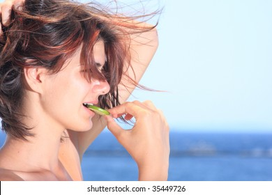 Beautiful young woman eating a lime slice
