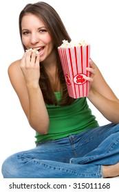 Beautiful young woman eating popcorn