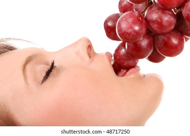 Beautiful young woman eating red grapes, isolated on white background