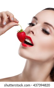 Beautiful young woman eating a strawberry. Portrait of a girl close-up. Red lips. Ripe strawberries. Isolation on a white background