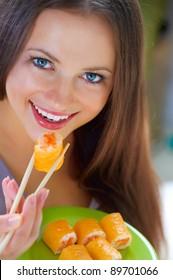Beautiful Young Woman Eating Sushi. Diet