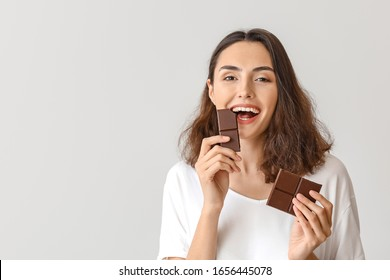 Beautiful young woman eating tasty chocolate on white background