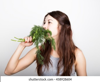 beautiful young woman eating an vegetables. holding cabbage, she stares at the head of cabbage. healthy food - healthy body concept.