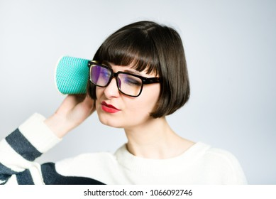 beautiful young woman eavesdropping, curious, short haircut, studio photo on background