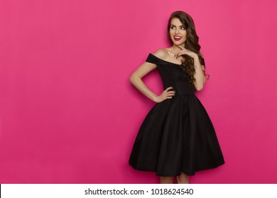 Beautiful young woman in elegant black cocktail dress is holding hand on chin, looking away and thinking. Three quarter length studio shot on pink background.