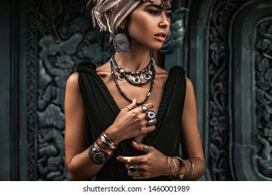 beautiful young woman in elegant black dress wearing turban. oriental princess
