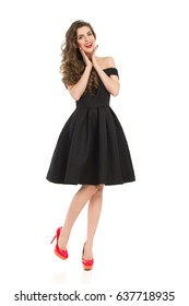 Beautiful young woman in elegant black cocktail dress and red high heels is standing on one leg, holding head in hands and looking at camera. Front view. Full length studio shot on isolated on white.