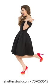 Beautiful young woman in elegant black cocktail dress and red high heels is standing on one leg, holding arms outstretched, shouting and looking away. Full length studio shot on isolated on white.