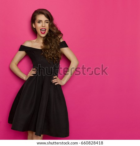 a4589d556ca Beautiful young woman in elegant black cocktail dress is holding hands on  hip