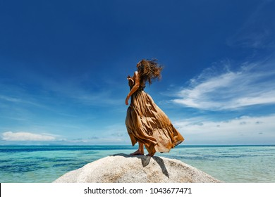 beautiful young woman in elegant dress on the beach