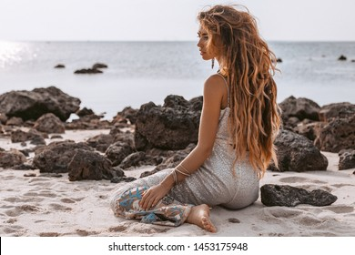 beautiful young woman in elegant dress sitting on the beach at sunset