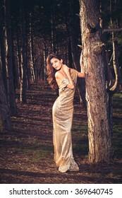 beautiful young woman in elegant glittering golden dress  in wood full body shot