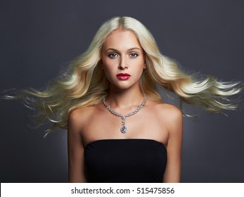 beautiful young woman with elegant hairstyle and jewelry. woman with flying hair. Blonde girl. Fashion beauty woman