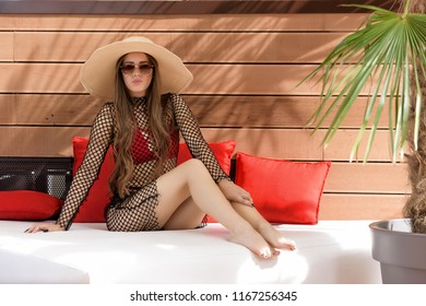 Beautiful young woman with elegant hat and sunglasses posing