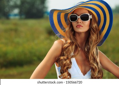 Beautiful young woman in elegant hat and sunglasses posing outdoor.