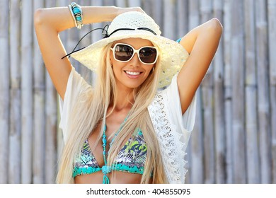 Beautiful young woman in elegant hat and sunglasses posing outdoor