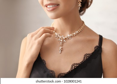 Beautiful young woman with elegant jewelry on grey background, closeup