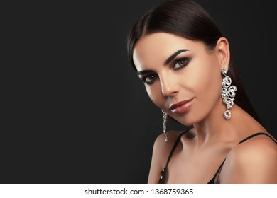 Beautiful young woman with elegant jewelry on dark background. Space for text