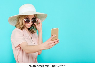 Beautiful young woman in elegant pale pink dress, sunglasses and summer hat taking selfie. Studio portrait of fashionable woman. Summer Vacation concept.