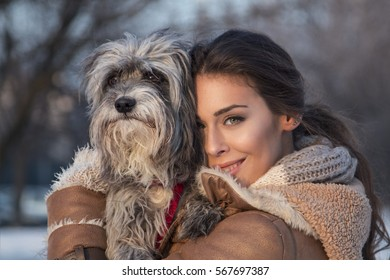 Beautiful young woman embrace her dog in park