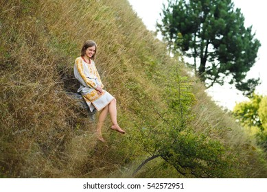 beautiful young woman in embroidered dress sitting on nature