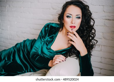 Beautiful young woman in emerald velvet dress sitting on a white couch