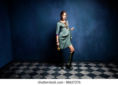 beautiful young woman in empty room standing holding flower in one hand