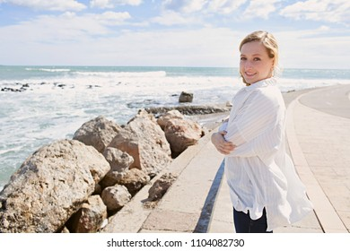 Beautiful young woman enjoying blue sunny sky by the sea wearing shirt floating in the breeze, well being calm living outdoors. Healthy natural female in coastal space, leisure recreation lifestyle.
