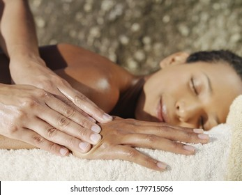 Beautiful young woman enjoying a body massage lying with her eyes closed in bliss on a fresh white towel in a spa or beauty clinic while the masseuse massages her hand