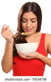 Beautiful young woman enjoying breakfast cereal