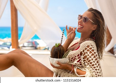Beautiful young woman enjoying a cocktail in a cabana on vacation