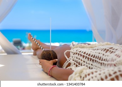 Beautiful young woman enjoying a cocktail in a cabana view on the ocean