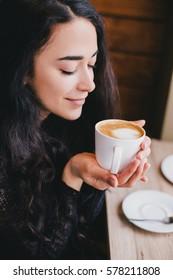 Beautiful young woman enjoying coffee cappuccino with foam near window in a cafe