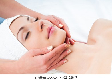 beautiful young woman enjoying facial massage in spa salon with eyes closed
