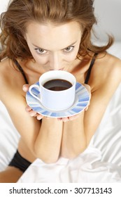 Beautiful young woman enjoying fresh coffee in bed at home