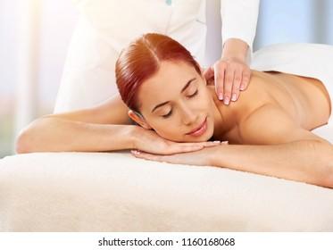 Beautiful young woman enjoying head massage in spa center