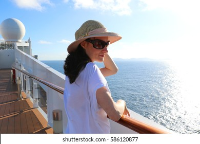Beautiful young woman enjoying her vacation on a luxury cruise by the Brazilian coast. Wonderful time to appreciate the sun, sea and blue sky. Huge Italian ship in Brazil for summer holidays.
