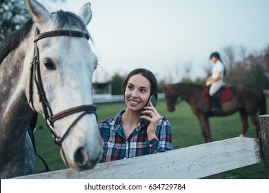 Beautiful young woman enjoying with her horse and talking on phone at ranch.