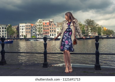 Beautiful young woman enjoying the journey, standing on the bridge in the background of the city of Amsterdam.