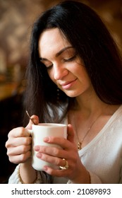 Beautiful young woman enjoying latte coffee in cafe