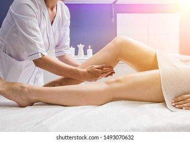 Beautiful young woman enjoying legs massage in spa salon. Cosmetology concept